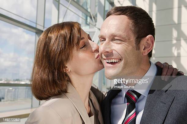 Mid adult couple, woman kissing man on cheek