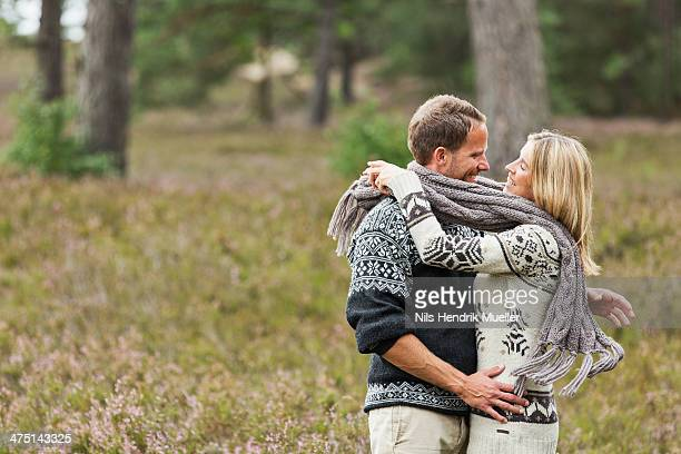 mid adult couple wrapped in scarf hugging - スカーフ ストックフォトと画像