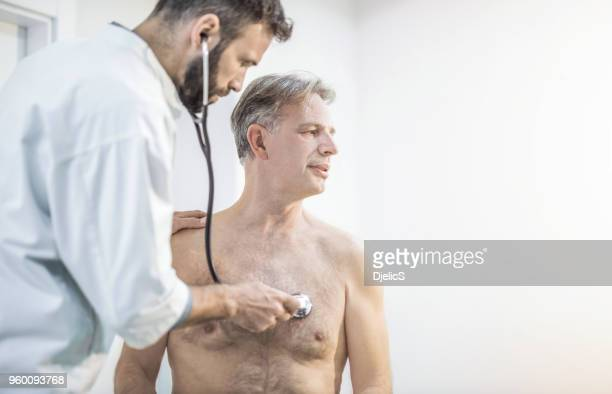 mid adult doctor examining his senior patient's chest. - chest barechested bare chested stock pictures, royalty-free photos & images