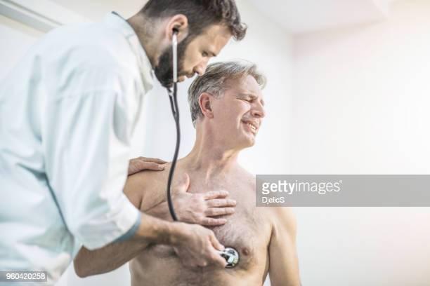 mitte erwachsenen arzt untersuchen senior woman schmerzhafte brust. - raucher lunge stock-fotos und bilder
