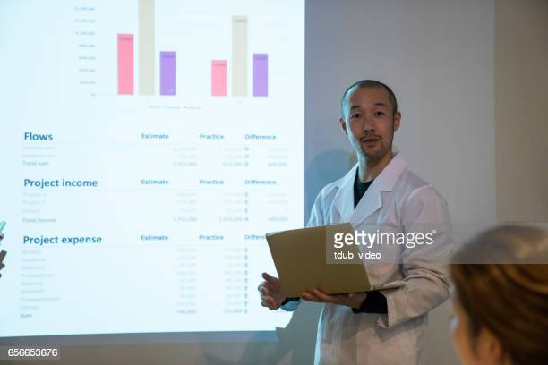 mid adult doctor giving a speech or presentation to colleagues - tdub_video stock pictures, royalty-free photos & images
