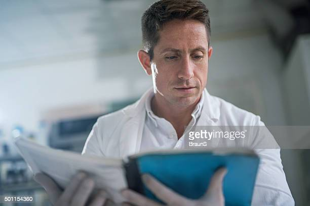Mid adult doctor reading medical data from a book.