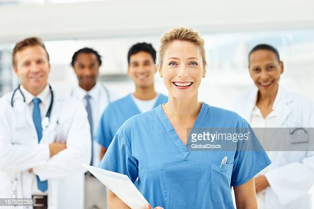 Mid adult doctor smiling with colleagues at the back