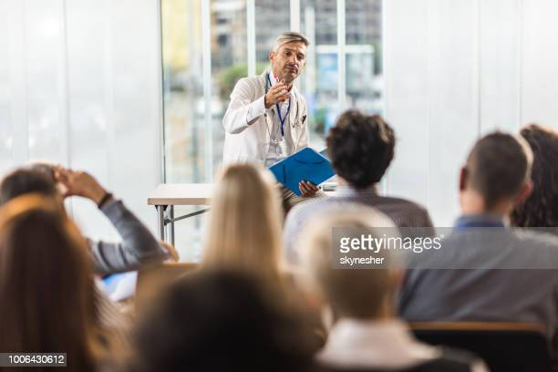 mid adult doctor teaching on a seminar in a board room. - seminario riunione foto e immagini stock