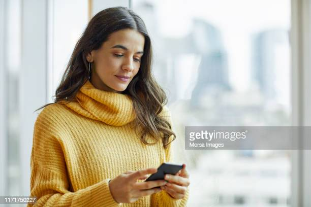 mid adult executive using smart phone at office - one mid adult woman only stock pictures, royalty-free photos & images
