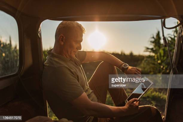 mid adult farmer inspects his land - land vehicle stock pictures, royalty-free photos & images