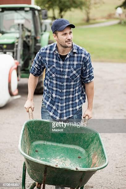 Mid adult farmer pushing wheelbarrow on rural road