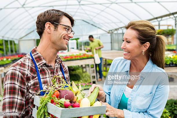 Mid adult farmer talks with customer about fresh produce