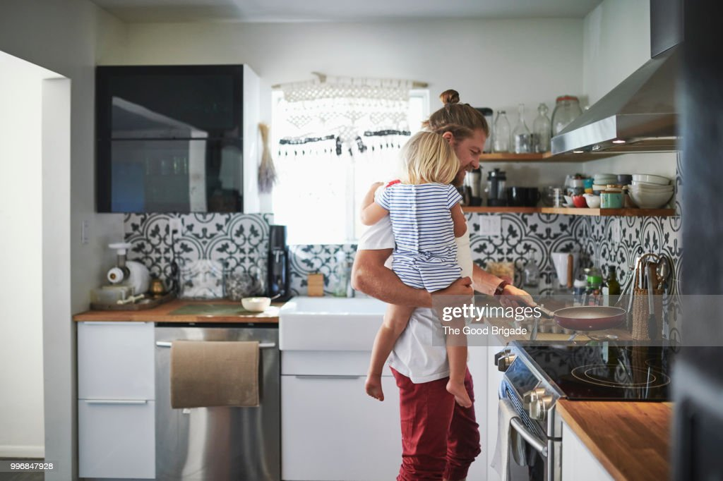 Mid adult father carrying daughter while cooking food in kitchen : Stock-Foto