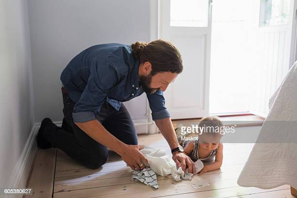 Mid adult father cleaning floor by baby boy at home