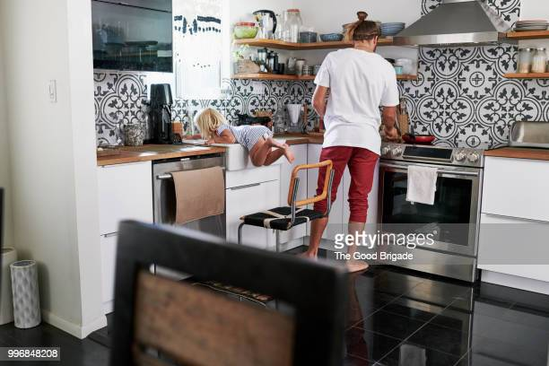mid adult father cooking food with playful girl in kitchen at home - naughty america stock pictures, royalty-free photos & images