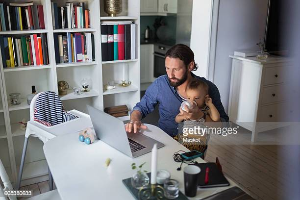 mid adult father feeding baby boy while using laptop at home - weekday stock pictures, royalty-free photos & images