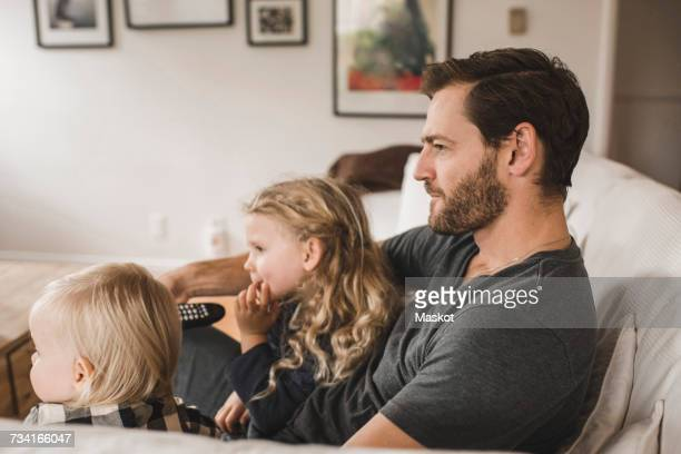 mid adult father with daughters watching tv in living room at home - contemplation family stock pictures, royalty-free photos & images
