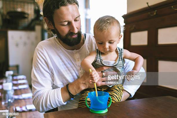 Mid adult father with son stirring spoon in cup at restaurant table