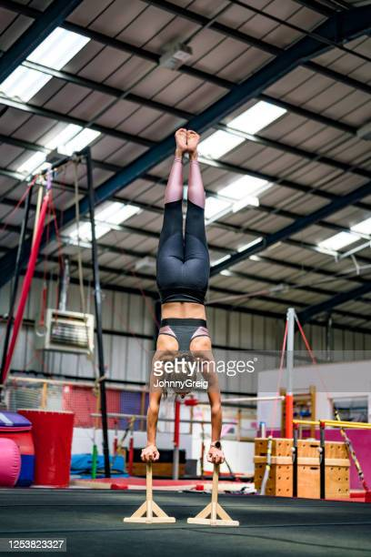 mid adult female athlete balancing on handstand canes in gym - floor gymnastics stock pictures, royalty-free photos & images