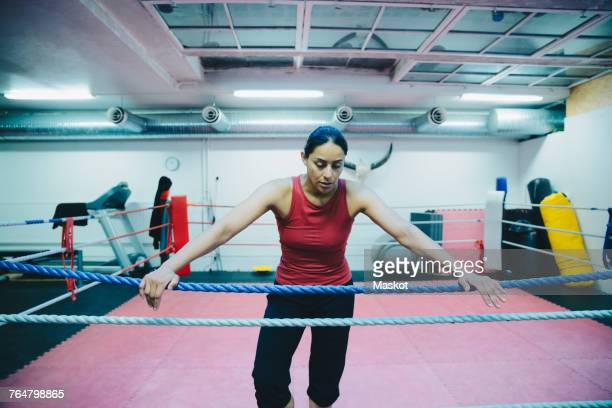mid adult female athlete leaning on boxing ring rope at health club - combat sport stock pictures, royalty-free photos & images