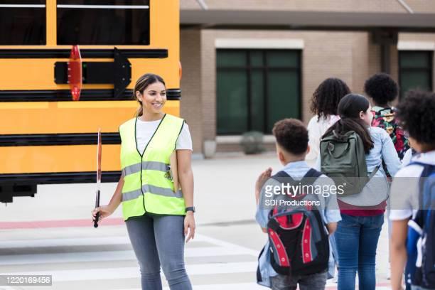 mid adult female crossing guard hört auf jungen jungen - staatliche schule stock-fotos und bilder