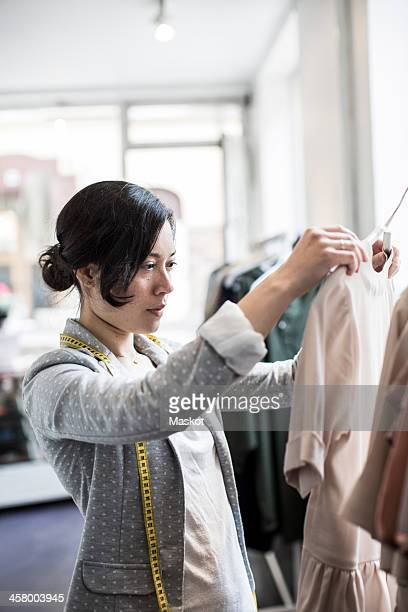 Mid adult female design professional analyzing dress in studio