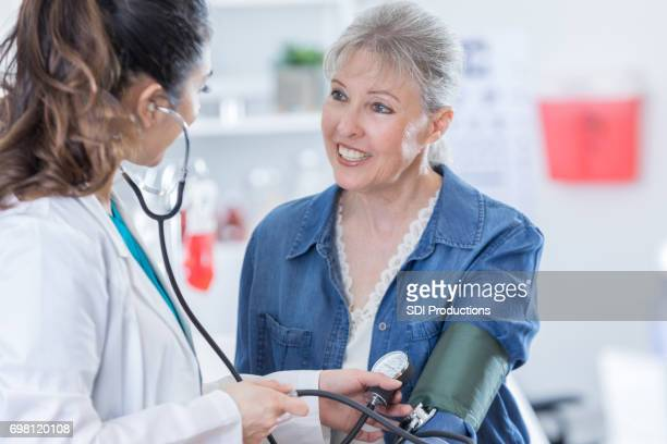 mid adult female doctor check's patient's blood pressure - blood pressure gauge stock pictures, royalty-free photos & images
