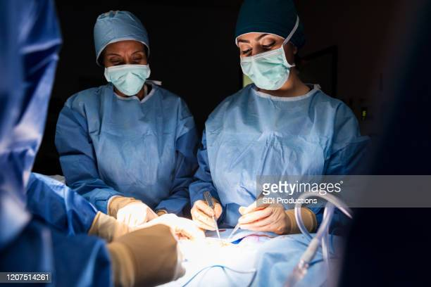 mid adult female doctor performs surgery under bright light - outpatient care stock pictures, royalty-free photos & images