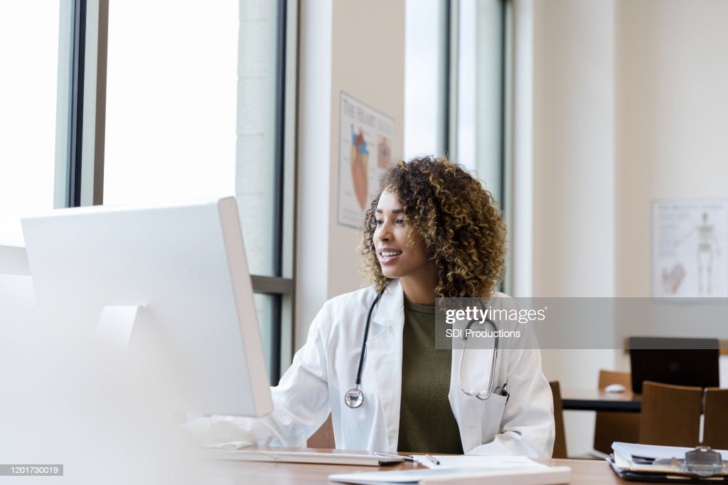 Mid adult female doctor reviews patient records on desktop PC : Stock-Foto