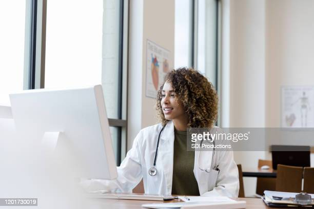 mid adult female doctor reviews patient records on desktop pc - computer foto e immagini stock