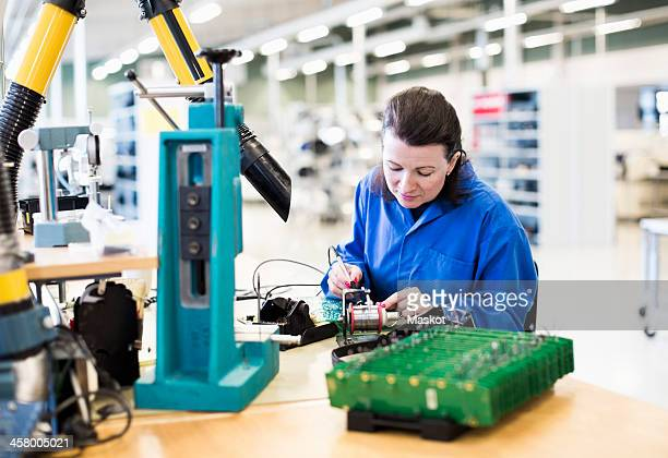 mid adult female electrician working on circuit board at desk in industry - electronics industry stock pictures, royalty-free photos & images
