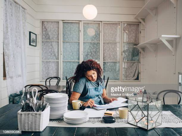 Mid adult female entrepreneur reviewing file while talking on mobile phone in restaurant