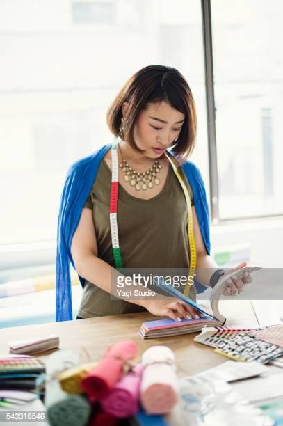 30 代の女性のファッション・デザイナーのスタジオで働く