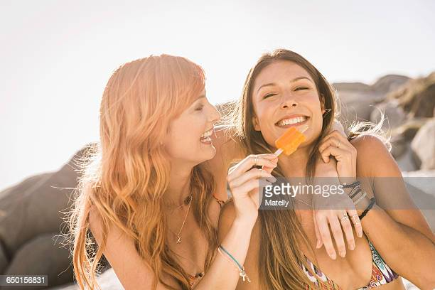 mid adult female friends eating ice lolly on beach, cape town, south africa - vrouwelijkheid stockfoto's en -beelden