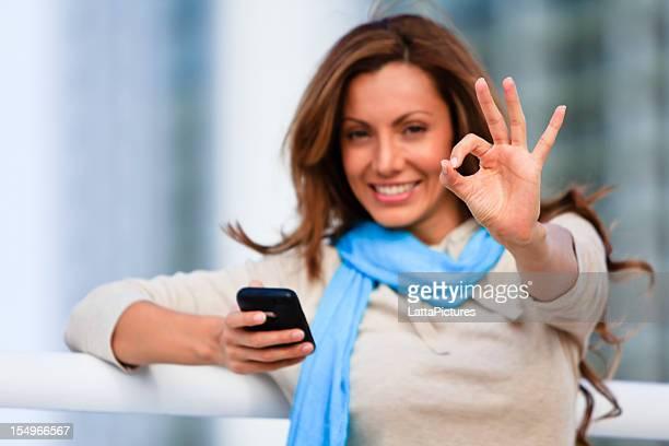 Mitte Erwachsene weibliche holding cellphone und geben OK Zeichen