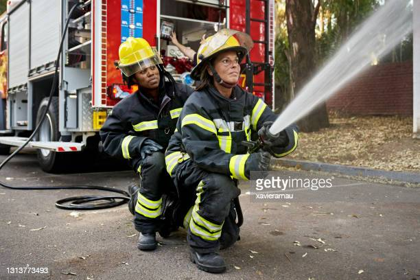 mid adult female hose team working at emergency site - firefighter stock pictures, royalty-free photos & images