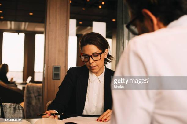 mid adult female lawyer discussing paperwork with client at table in office - legal system stock pictures, royalty-free photos & images
