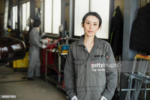 自動車で成人女性メカニックの作業半ば修理店 - オーバーオール ストックフォトと画像
