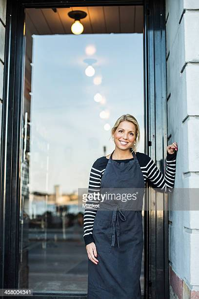 Mid adult female owner leaning on wall while standing against doorway