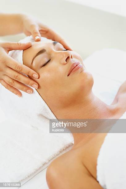 Mid adult female receiving facial massage in spa