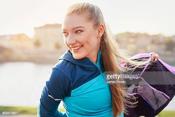 Mid adult female runner putting on tracksuit top at city riverside