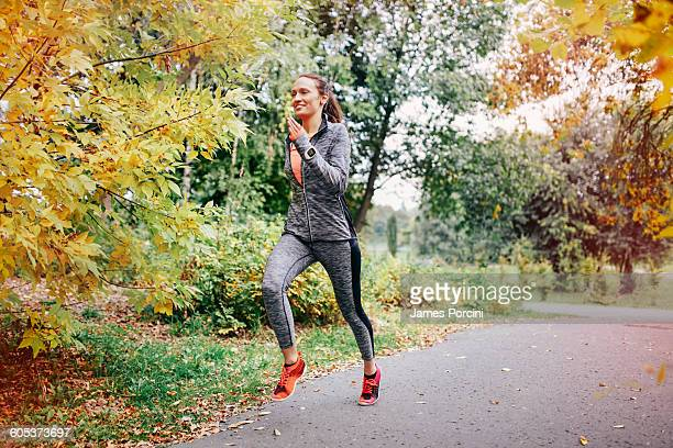 Mid adult female runner running along park path