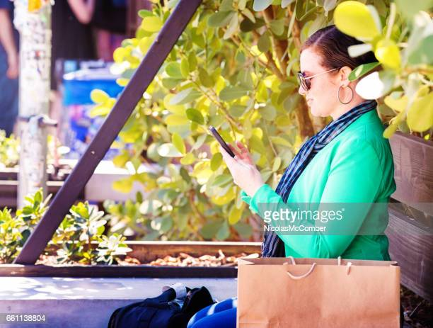 Mid adult female solving problems on mobile phone while sitting in a park