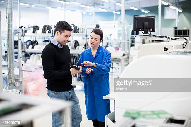 Mid adult female technician explaining machine part to client in factory