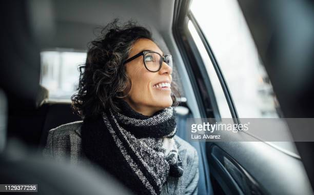 mid adult female traveling by a car - passenger stock pictures, royalty-free photos & images