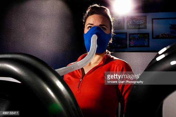 Mid adult female with face mask on gym treadmill in altitude centre