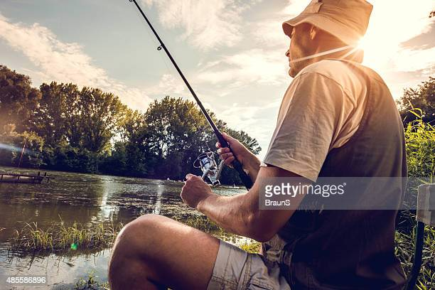 Mid adult fisherman river fishing at sunset.
