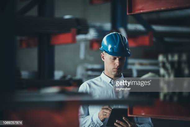 Mid adult foreman working on digital tablet in aluminum mill.