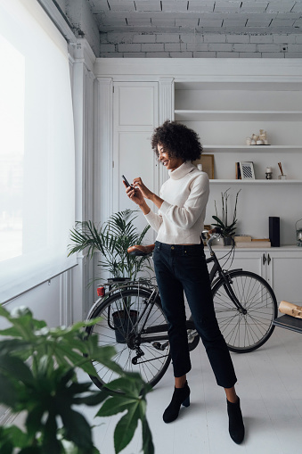 Mid adult freelancer standing in her home office, using smartphone - gettyimageskorea