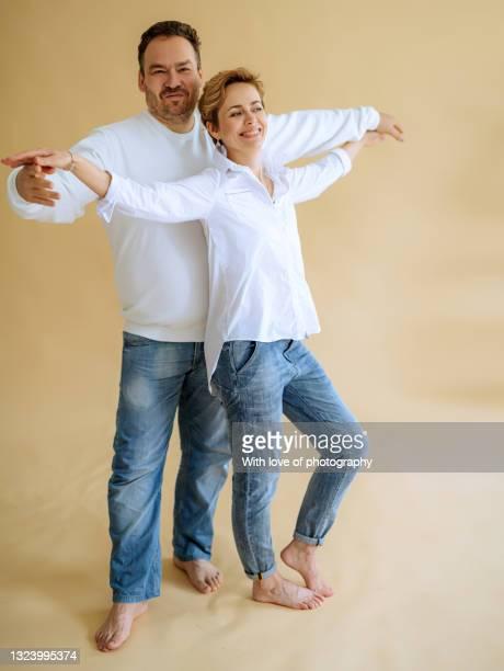 mid adult heterosexual couple on beige background 40-44 years - 30 34 years stock-fotos und bilder
