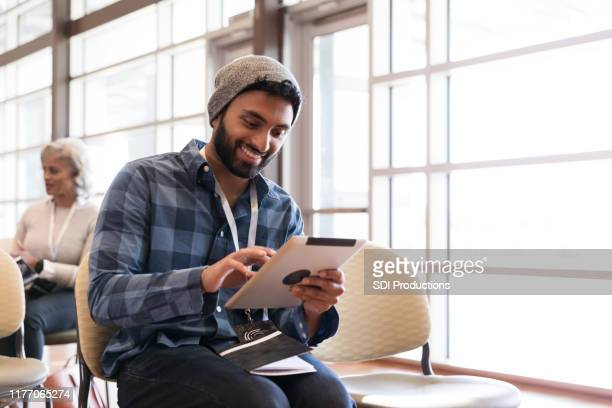 mid adult hipster smiles as he looks at digital tablet - town hall stock pictures, royalty-free photos & images