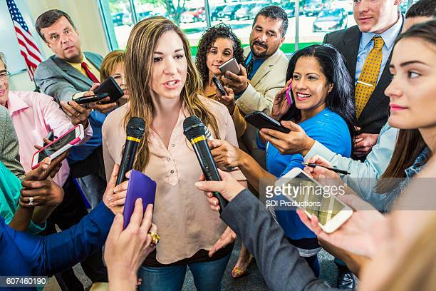 mid adult hispanic female politician answers questions after her speech - local politics stock pictures, royalty-free photos & images