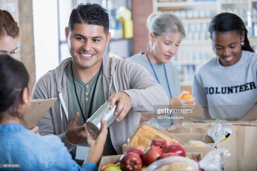 Mid adult Hispanic man volunteers during food drive : Stock Photo