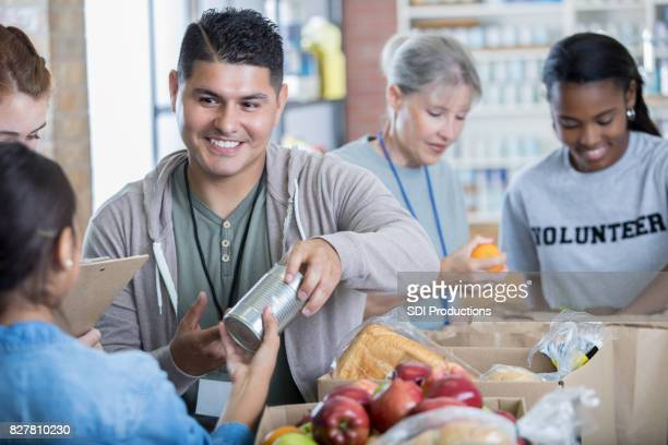mid adult hispanic man volunteers during food drive - charity benefit stock pictures, royalty-free photos & images